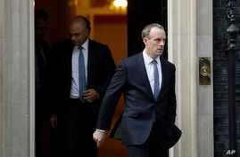 FILE - Britain's Secretary of State for Exiting the European Union Dominic Raab, right, leaves 10 Downing Street in London, Oct. 24, 2018.