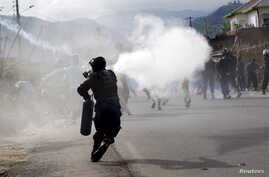 A riot police officer sprays teargas on residents participating in street protests against the decision made by Burundi's ruling party to allow President Pierre Nkurunziza to run for a third five-year term, in the capital Bujumbura, April 26, 2015.