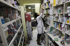 FILE - An Iranian pharmacist arranges medicine on shelves at a pharmacy in central Tehran, Iran, Dec. 11, 2012. The strength of the U.S. dollar and concerns that the U.S. will again impose tough economic sanctions have prompted the price of pharmaceu
