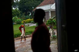A pregnant 15-year-old girl who was the victim of statutory rape, stands in a doorway of the house where she stays in Masaka, Uganda, May 30, 2017. She is having difficulty pressing charges against the perpetrator because she cannot prove that she is