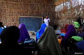 Zeinab's English teacher Abdiweli Mohammed Hersi teaches children at the school near a camp for internally displaced people from drought hit areas in Dollow, Somalia, April 3, 2017.