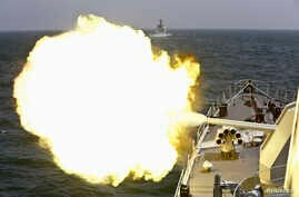 A Chinese navy vessel fires its cannon during the Joint Sea-2014 naval drill outside Shanghai on the East China Sea, May 24, 2014. Chinese and Russian navies staged exercises on the East China Sea on Saturday to simulate anti-submarine and search-and