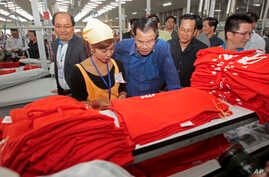 Prime Minister Hun Sen, center, leans over a garment worker during a visit to a factory outside of Phnom Penh, Cambodia,  Aug. 30, 2017.