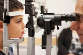 Dr. Albert Maguire checks the eyes of Misa Kaabali, 8, at the Children's Hospital of Philadelphia, Oct. 4, 2017. Misa was 4 years old when he received his gene therapy treatment.