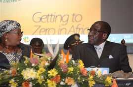 Zimbabwean Deputy Prime Minister Khupe, left, chats with President Mugabe at a women's empowerment event, Harare, May 24,2012.