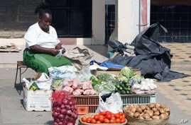FILE - A woman roadside vegetable vendor displays her goods as the price of vegetables has doubled along with other foodstuffs since election day in Nairobi, Kenya, March 7, 2013.
