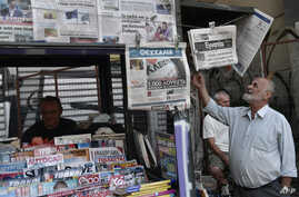 "FILE - A man reads newspapers' headlines at a kiosk in central Athens, Aug. 21, 2018, the day Greek Prime Minister Alexis Tsipras called a ""day of redemption"" as he hailed the end of his country's eight-year ""odyssey"" of painful bailouts. On Monday,"