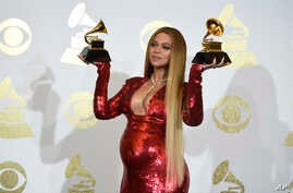 """Beyonce poses in the press room with the awards for best music video for """"Formation"""" and best urban contemporary album for """"Lemonade"""" at the 59th annual Grammy Awards at the Staples Center, Feb. 12, 2017, in Los Angeles."""