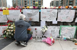 Jack Young leaves a notes on April 24, 2018, at a makeshift memorial for victims in the van attack in Toronto, Ontario.  A van driver who ran over 10 people when he plowed onto a busy Toronto sidewalk was charged with murder Tuesday, as Canadian Prim