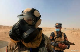 Iraqi forces wear protective masks after winds brought fumes from a nearby sulfur plant set alight by Islamic State militants, south of Mosul in Qayyara, Iraq, Oct. 22, 2016.
