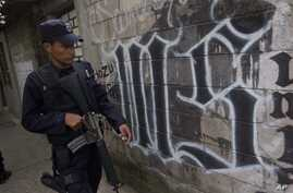 "FILE - A member of the Salvadoran National Police walks next to symbol of the ""Mara Salvatrucha"" gang painted on a wall during an anti-gang operative in San Salvador, El Salvador."