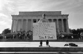 A man stands in front of Lincoln Memorial in Washington, D.C., with a message against President Trump on Presidents' Day, Feb. 20, 2017. (Sama Dizayee/VOA Kurdish)