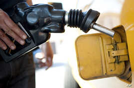 FILE - A customer pumps gas into his dual-tank pickup truck at a 76 gas station in Los Angeles, Aug. 10, 2012.