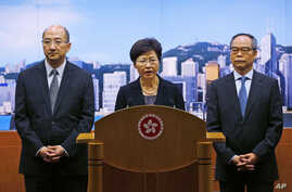 From left, Hong Kong Secretary for Constitutional and Mainland Affairs Raymond Tam Chi-yuen, Chief Secretary Carrie Lam and Constitutional Affairs Undersecretary Lau Kong-wah hold a news conference in Hong Kong, Oct. 9, 2014.