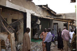 People inspect houses damaged damaged in Saturday's rocket-propelled grenades by Islamic extremist in Maiduguri, Nigeria, May 31, 2015.