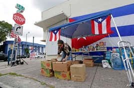 Volunteer Teresa Cruz places donated food items in a box for hurricane relief bound for Puerto Rico, Sept. 27, 2017, in the Little Havana area in Miami.