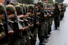 FILE - Turkish soldiers take part in the annual military parade in the Turkish-controlled northern part of Nicosia in this ethnically divided island of Cyprus, July 20, 2016.