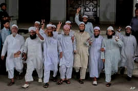 Leaders of a Bangladeshi Islamic group flash victory signs after Bangladesh's top court rejected a 28-year-old petition Monday to remove Islam as the official religion of the Muslim-majority South Asian nation in Dhaka, Bangladesh, March 28, 2016.
