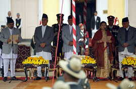 FILE - Kalyan Shrestha, left, Nepal's chief justice at the time, administers the oath of office to newly elected President Bidhya Bhandari, fourth from left, in the presence of other officials  (4th L) in the presence of other officials at the presid