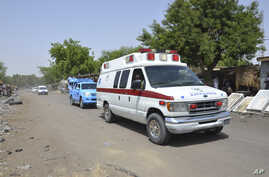 FILE - An ambulance and security vehicles are seen driving to the site of a June 2, 2015, suicide bomb attack in Maiduguri, Nigeria.