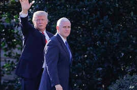 FILE - President Donald Trump, accompanied by Vice President Mike Pence, left, waves to members of the media as they walk to the Oval Office of the White House in Washington, Jan. 25, 2017