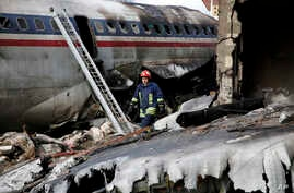 This photo provided by Mizan News Agency, shows an Iranian rescue works at the site of a Boeing 707 cargo plane crash, at Fath Airport about 40 kilometers (25 miles) west of Tehran, Iran, Jan. 14, 2019.