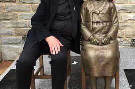 Uniting Church minister Bill Crews poses for a photo with a statue erected as a memorial to sex slaves of Japan's World War II army in Sydney, Australia, Aug 6. 2016. A Japanese-Australian community leader said Thursday he had filed a complaint of ra