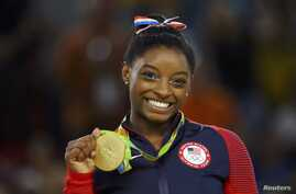 FILE - US gymnyst Simone Biles poses with her gold medal for artistic gymnastics during the victory ceremony at the Rio Olympic Arena in Rio de Janeiro, Brazil, Aug. 16, 2016.