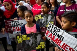 FILE - In this June 26, 2018, photo, children stand and hold protest signs during a rally in front of Federal Courthouse in Los Angeles.