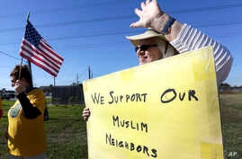 Jane Malin holds a sign as she waves to passing cars during a rally to show support for Muslim members of the community near the Clear Lake Islamic Center in Webster, Texas, Dec. 4, 2015.
