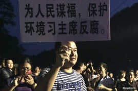 A demonstrator holds a placard during a protest against the construction of a waste incinerator in Hangzhou, Zhejiang province May 7, 2014.