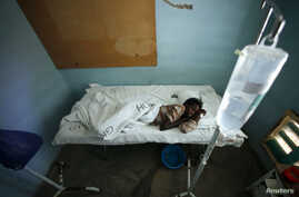 Mariam Dagane, who is infected with Rift Valley Fever, rests on her bed at the Garissa hospital, 390 km (242 miles) north-east Nairobi, January 9, 2007.  Rift Valley Fever, a highly contagious virus, has killed 74 people in Kenya and infected hundred