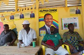 People sit inside a local restaurant displaying posters for Guinea's incumbent President Alpha Conde, in Conakry, Guinea, Oct. 17, 2015.