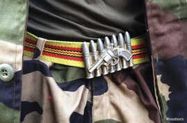 FILE - A soldier from the Seleka rebel coalition wears a belt buckle in the design of a gun and ammunition in Bangui.