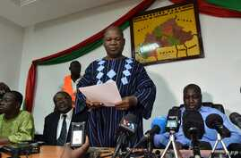 Opposition leader Jean Hubert Bazie (C) reads a  statement, next to the head of Burkina Faso's opposition Zephirin Diabre (D), during a press conference on Nov. 1, 2014 in Ouagadougou.