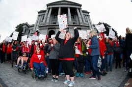 FILE - Stephanie Rolf, center, a teacher in the Douglas County, Colorado, school system, leads a cheer during a teacher rally in Denver, April 26, 2018.