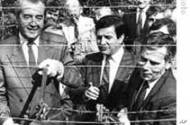 Hungarian Foreign Minister Gyula Horn (r) with Austrian counterpart Alois Mock cut through barbed wire of former Iron Curtain marking border between East, West in Sopron, Hungary, 27 Jun 1989