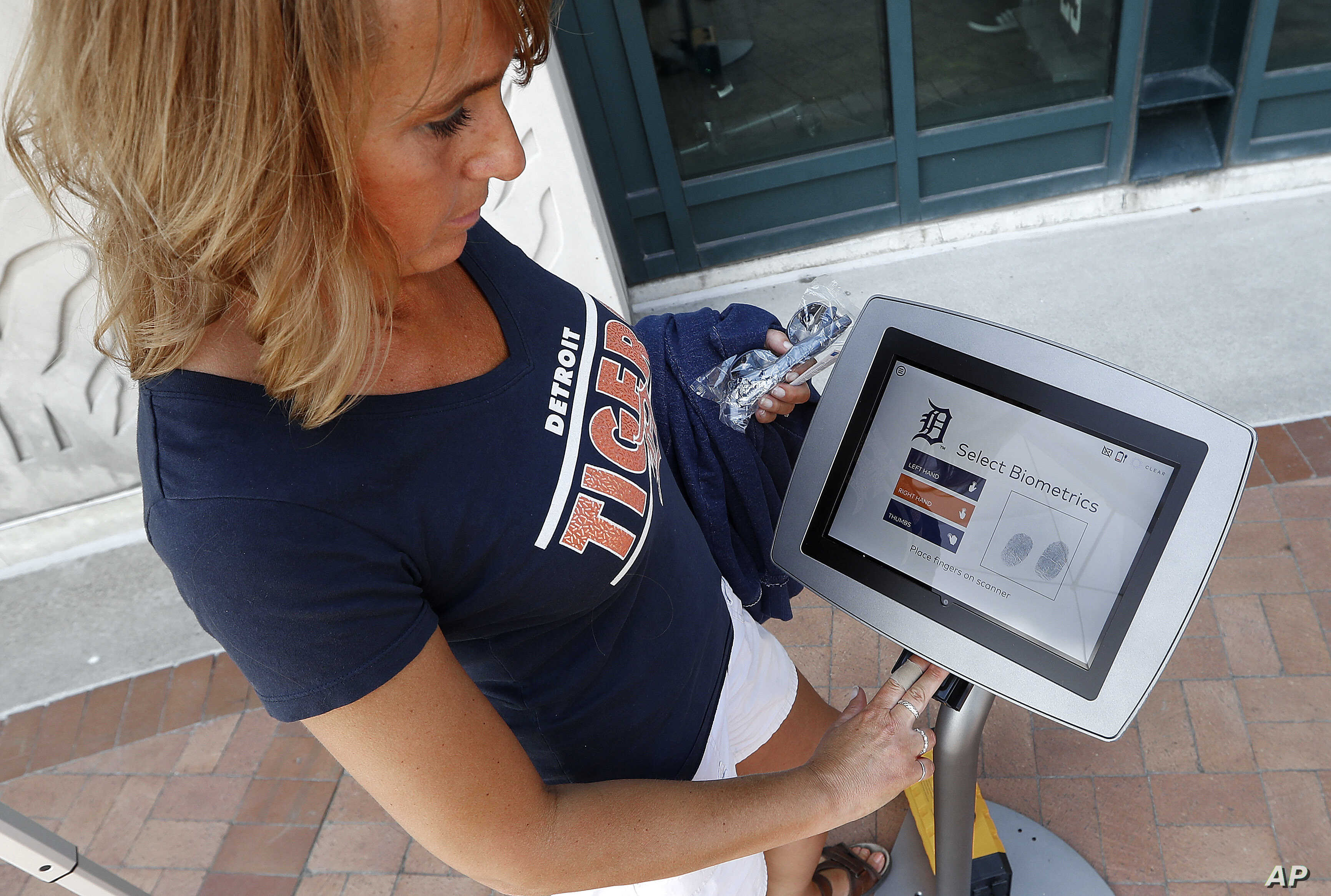 Jacquelyn Klimsza, of Fruitport, Mich., scans her fingerprints at a CLEAR biometric system outside Comerica Park before a baseball game between the Detroit Tigers and Kansas City Royals in Detroit,  July 25, 2017. The Detroit stadium is among the fir