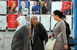 Women walk past a wall plastered with electoral campaign posters two days before the first round of the presidential elections in Tunis, Tunisia, Nov. 21, 2014.