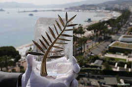 A Chopard representative displays the Palme d'Or, the highest prize awarded to competing films, during an interview before the start of the Festival, Cannes, France, May 7, 2018.