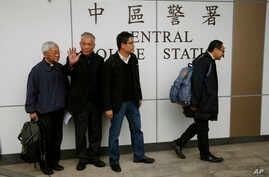 Four protest leaders, from right, Benny Tai Yiu-ting, Chan Kin-man, Chu Yiu-ming and former Cardinal Joseph Zen, walk inside the police station in Hong Kong as they surrender to police Wednesday, Dec. 3, 2014.