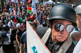A white nationalist demonstrator with a helmet and shield walks into Lee Park in Charlottesville, Va., Aug. 12, 2017. Hundreds of people chanted, threw punches, hurled water bottles and unleashed chemical sprays on each other Saturday after violence
