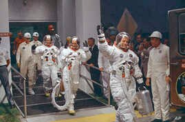 FILE - Neil Armstrong waving in front, heads for the van that will take the crew to the rocket for launch to the moon at Kennedy Space Center in Merritt Island, Fla., July 16, 1969.