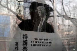 "A man reading a newspaper posted on a public bulletin board is reflected in the glass, in Beijing, Jan. 3, 2017. The photo of U.S. President-elect Donald Trump is published with an article that reads ""Trump uses fist to talk."""