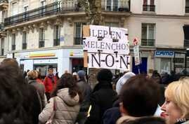 A marcher brandishes a sign against both far-right leader Marine Le Pen and far-left leader Jean-Luc Melenchon, both of whom critics accuse of anti-semitic discourse.