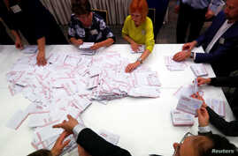 Election officials count votes during a general election in Riga, Latvia, Oct. 6, 2018.