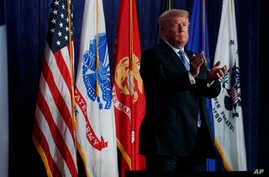 """President Donald Trump claps after speaking during a """"Salute to Service"""" dinner, July 3, 2018, in White Sulphur Springs, West Virgina."""
