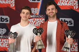 "Drew Taggart, left, and Alex Pall, of the Chainsmokers, pose with the awards for best new artist, best new pop artist and dance song of the year for ""Closer"" in the press room at the iHeartRadio Music Awards at the Forum on March 5, 2017."