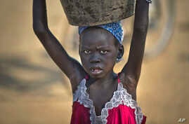 A young displaced girl carries a bucket of water back to her makeshift shelter at a United Nations compound which has become home to thousands of people displaced by the recent fighting, in the Jebel area on the outskirts of Juba, South Sudan Tuesday
