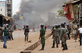 Guinea security forces, center, face people rioting and burning rubbish and other goods in the streets of Conakry, April 13, 2015.